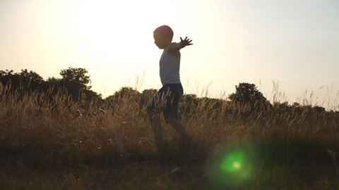 Young boy with raised as airplane hands running on green grass at the field on sunny day. Child jogging at the lawn outdoor. Happy male kid having fun in nature on summer meadow. Slow motion Close up