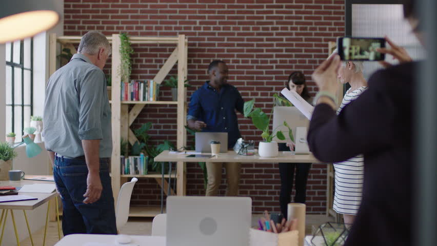 Multi ethnic business team dancing excited celebrating successful company start up happy coworkers cheering arms raised in modern office workspace | Shutterstock HD Video #1010156990