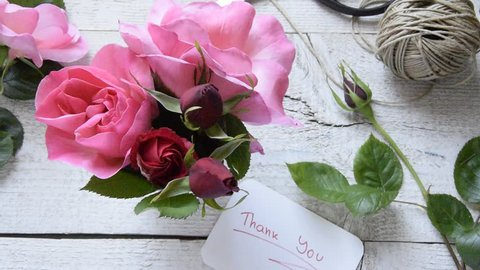 "Top view of female decorator leaving ""Thank you"" card, arranging roses on the wooden table, Concepts - fiorist, occupation, hobby, small business"