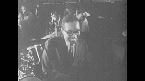 1960s: Jazz trio plays instruments on small stage. The Billy Taylor Trio plays for audience. Audience applauds.