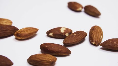 Nuts of almonds fall on a white table. Slow motion.