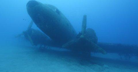 scuba divers exploring air plane wreck underwater