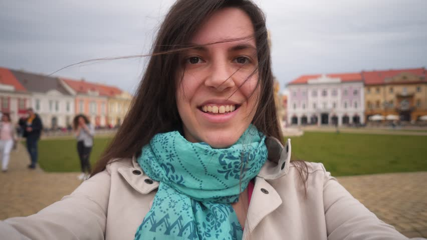 Girl making selfie video vlog at Timisoara. Young brunette woman stands at a city square, records video vlog, point of view. Shot at city of Timisoara, Romania,