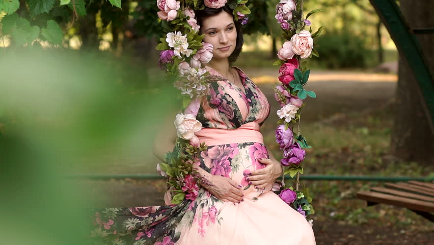 Happy pregnant woman in a flower wreath sits on swing in summer Park at sunset. Young beautiful pregnant girl in a long dress with flowers sits on a swing decorated with flowers.   Shutterstock HD Video #1010185760