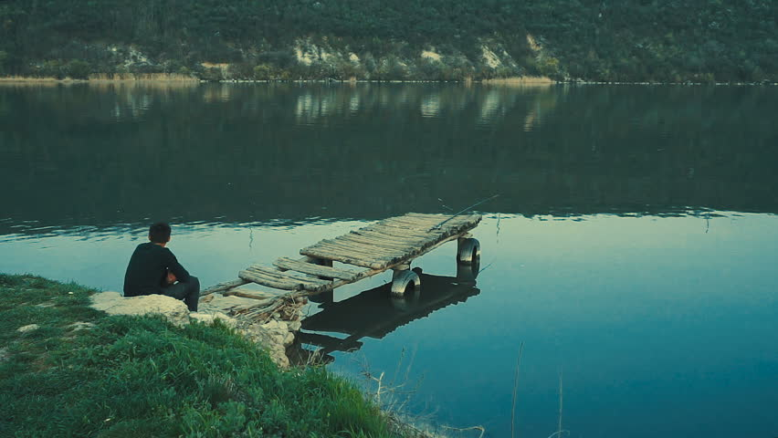 The man seated at the river (lake) bank.   Shutterstock HD Video #1010193260