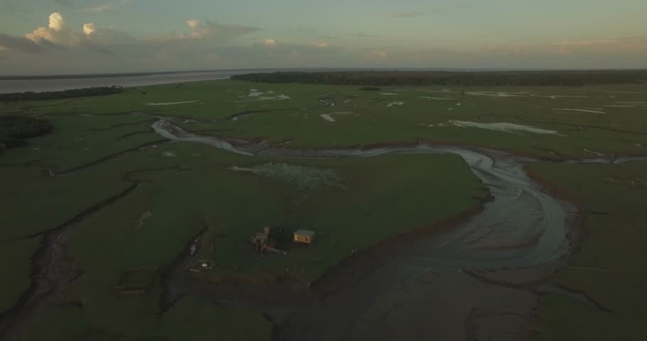 Aerial of Marajo Island Amazon River inlets and tributaries pulling back from a small stilt house in the background at low tide