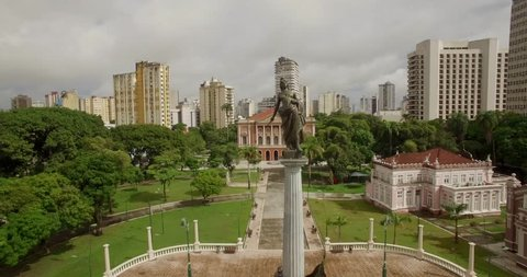Aerial passing statue on plinth in foreground to reveal The Peace Theatre, Teatro da Paz in Belem do Para, Amazon, Brazil