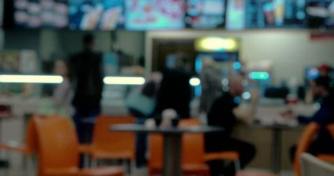 Defocused People in front of counter of fast food cafe in food court of shopping mall Vintage color grading