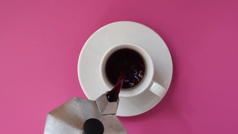 Pouring Coffee In a Cup. Pink table. Top view