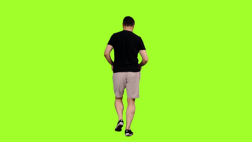 Rear view of a man in shorts and black t shirt jogging on green background, Chroma key, 4k shot