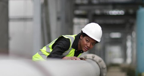 Female industrial worker checking pipeline