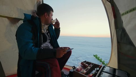 Man angler drinking hot tea and using tablet pc after successful winter fishing in tent on background beautiful sky and frozen lake. Fisherman resting in winter tent while beautiful sunset