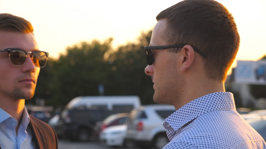 Two young business men standing outdoor and talking. Businessmen in sunglasses meet and speaking outside in the city. Communication of serious colleagues in car parking. Close up Slow motion