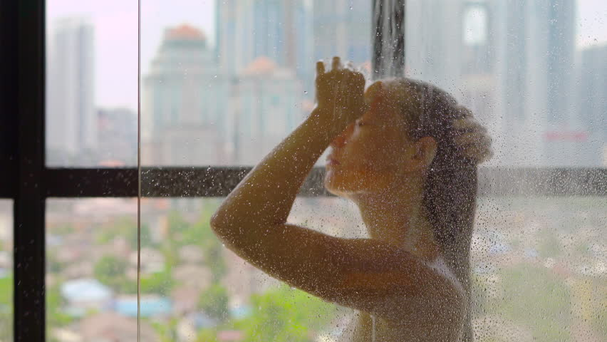 Young woman takes a shower in the bathroom with panoramic windows and silhouettes of skyscrapers outside the window