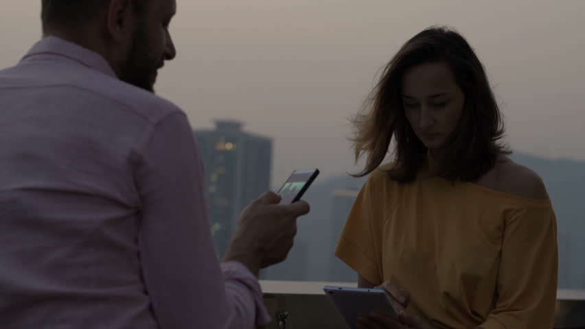 Young couple with smartphone and tablet talking on terrace in bar  #1010289890