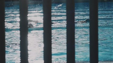 Slow motion shot of professional athletes training in swimming pool, swim the breaststroke style, morning workout for healthy lifestyle, gym membership sport activity.May 20018 in Barcelona, Spain