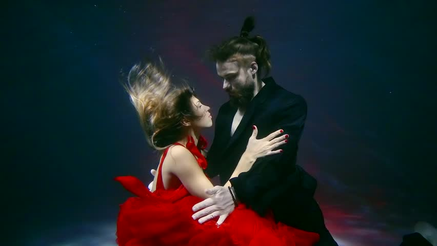 young woman dressed in red dress swims with her lover under water, couple hugs #1010307740