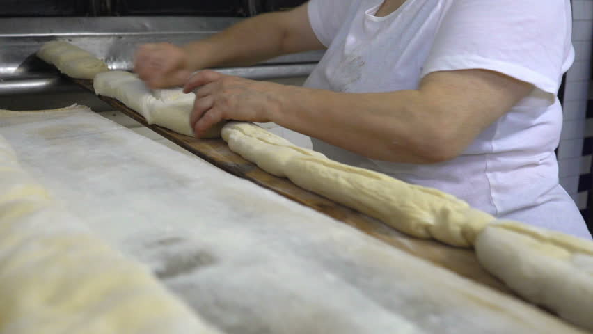 Traditional Italian family bakery. The woman Baker puts the bread in the oven for baking by using a special long Board. Real people. | Shutterstock HD Video #1010317490