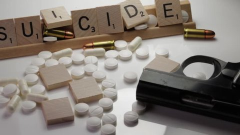 Toronto, Canada 2018: Suicide and Mental Health Awareness concept Suicide spelled in text with shell casings, pills,and gun. Concept of Veteran Soldiers suffering from shell shock.