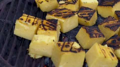 Closeup sliding to the right of polenta on a hot grill with smoke rising.