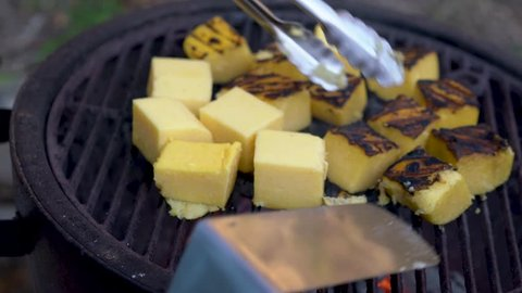 Using tongs someone flips over pieces of polenta on the grill.