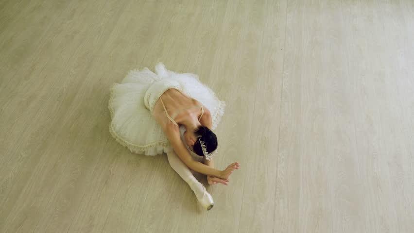 Classical ballet. Top view of ballerina dancing in pointe shoes in dance studio.