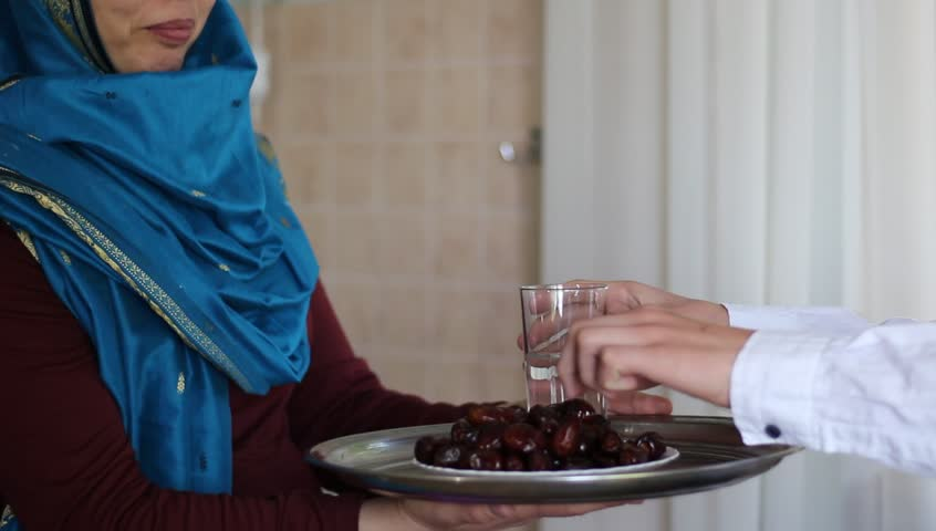 Roza Ramadan Time. Husband and wife. A glass of water and ripe dates - a food that is consumed while breaking fast during holy month of Ramadan