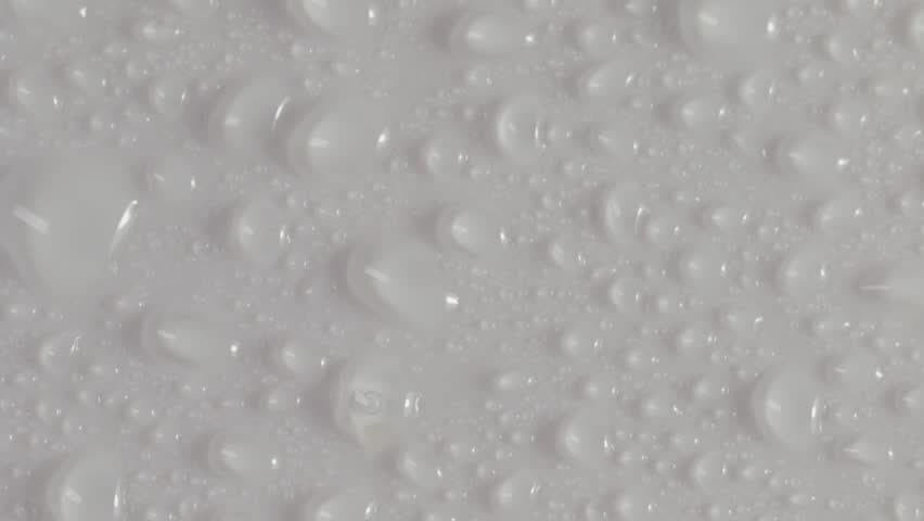 Water texture. Drops of moister and dew. Isolated water drops on white background. Clear rain water collecting on a waterproof surface. Wet background texture up close.
