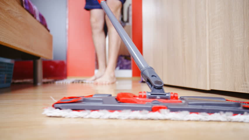 Person cleaning bedroom floor low angle slow motion 4K. Static shot of wet mop in focus moving in front the lens on the floor. Bed on left side and closets on the right. | Shutterstock HD Video #1010444480