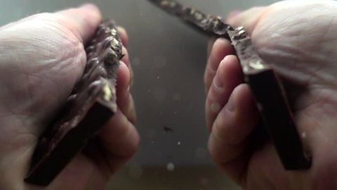 Hands break a bar of chocolate. Slow-motion shooting of 960 frames per second