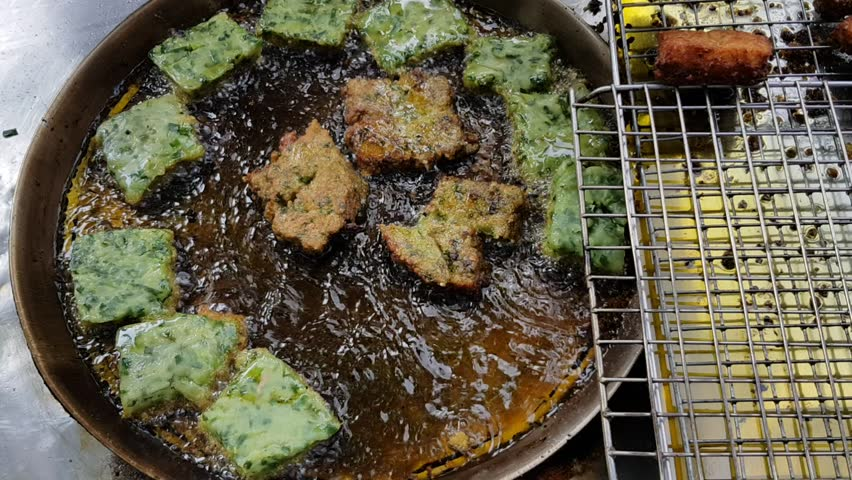 Chinese chives dumplings are fried in the pan. Someone use cooking spatula/turner to fried vegetable chives dumpling. Chive dumplings are Thai-Chinese street food and snacks.