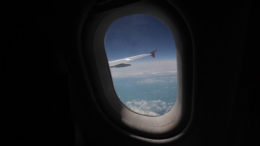 View of the blue sky and clouds through the window of the aircraft, Airplane window with airplane wing, Closeup