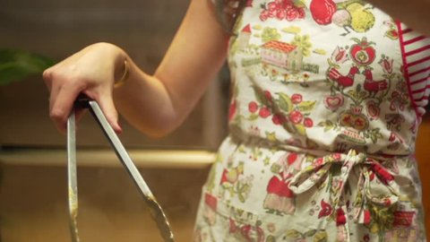 Close-up shot of a female chef sprinkling chopped basil into a pan cooking a pasta dish and then mixes it in.