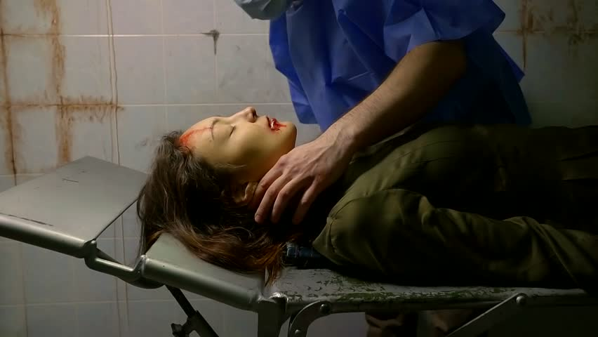 a portrait of a woman who lies on a gurney in a strange ambulance, the doctor examines the patient's face