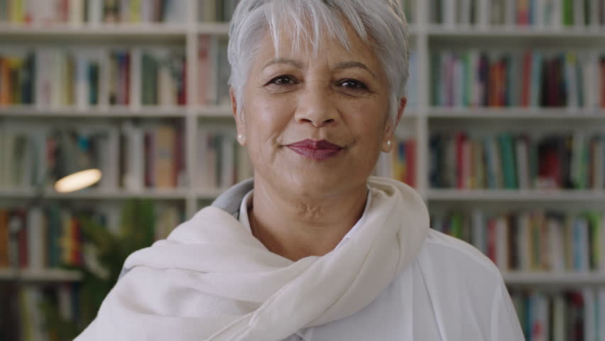 Portrait of confident friendly indian middle aged teacher standing in library close up | Shutterstock HD Video #1010501450