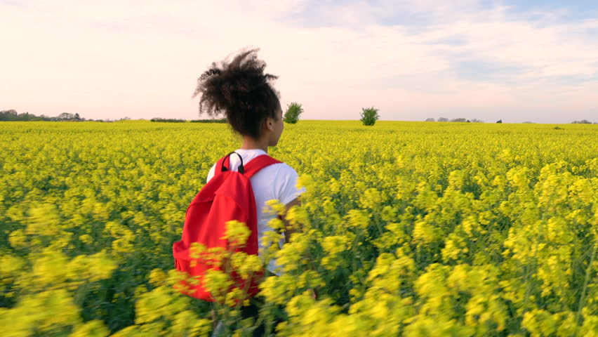4K tracking video clip of beautiful happy mixed race African American girl teenager female young woman hiking with red backpack and bottle of water in field of rape seed yellow flowers