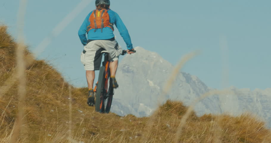 Mountain biker riding his bicycle up hill to the top of the mountain. #1010578310
