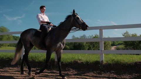 young man ride horse farm animal with blue sky in background. Slow motion
