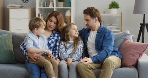 Caucasian happy family sitting on the cozy couch in the living room and talking with their small cute kids who sitting on their knees and between them. Indoor