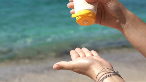 SLOW MOTION: Girl squeezing sun protect cream. Young woman holds a tube of sunblock product, squeezing it out on palm of her hand. Shot at Thassos island, Greece.