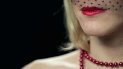 Sexy widow applying red lipstick on black background. Close up
