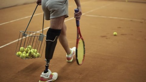 Tracking footage of a sports girl with a prosthesis on her right foot picking up tennis balls with the basket. Tennis player. Back view
