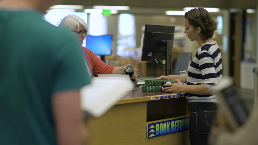 Students returning books to librarian in college library.