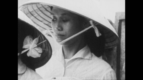 VIETNAM 1960s: Women in coolies smile and talk. Hands exchange money and weigh produce on scales. Women work at market. Hands exchange money and gods. Women smile and weigh vegetables at market.