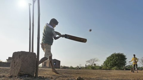 A slow motion shot of underprivileged village boy playing cricket in open field with bare feet. A young rural kid hits the cricket ball with a bat. group of children enjoying summer holidays