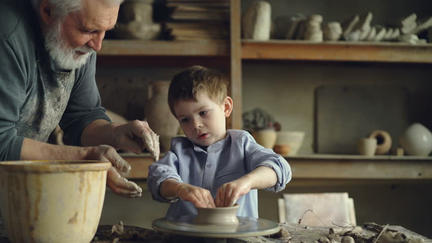Diligent young learner is shaping clay pot under the guidance of his experienced male teacher. Apprenticeship, traditional pottery and childhood concept.