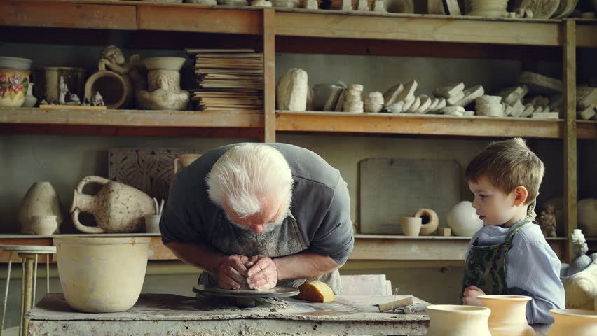 Caring senior grandfather is showing young grandson how to work with clay on throwing-wheel in small workshop. Pottery, family hobby and handicraft concept.