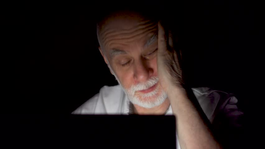 Tired senior businessman at home working on laptop late at night. Secretly using computer hiding from people. Stressed overworked having severe headache. Dark only face illuminated | Shutterstock HD Video #1010635820