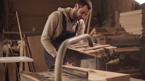 The craftman is working on electric saw machine. Sawing a large wooden bar. Dust and chips are scattering