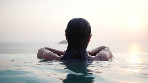 Beautiful attractive girl with sunglasses resting and swimming in a luxury infinity pool with stunning views during sunset. Slow motion